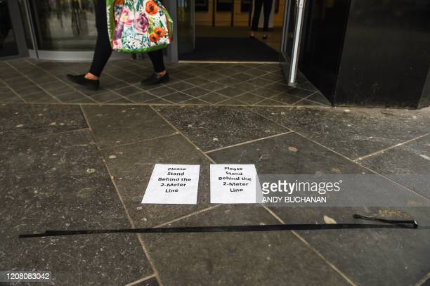A picture shows tape on the floor to aid social distancing while people queue to enter a shop in Glasgow on March 24 2020 after Britain ordered a...