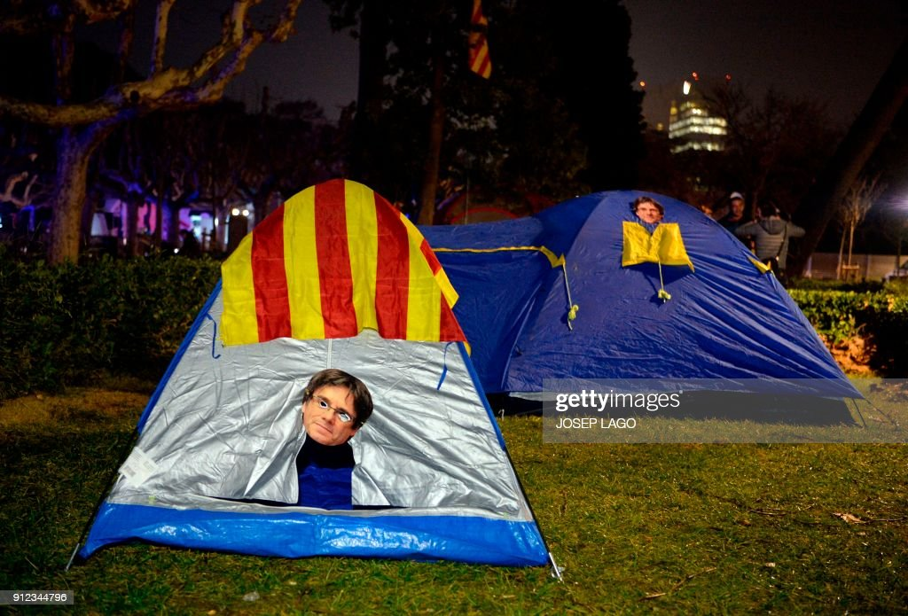 TOPSHOT - Picture shows tents with masks depicting ousted separatist leader Carles Puigdemont, set up outside the Catalan parliament at the Ciutadella park on January 30, 2018 in Barcelona. The speaker of Catalonia's parliament Roger Torrent delayed a key debate in the regional assembly on ousted separatist leader Carles Puigdemont's bid to form a new government, but defended his right to return to power. / AFP PHOTO / Josep LAGO