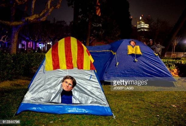 TOPSHOT Picture shows tents with masks depicting ousted separatist leader Carles Puigdemont set up outside the Catalan parliament at the Ciutadella...