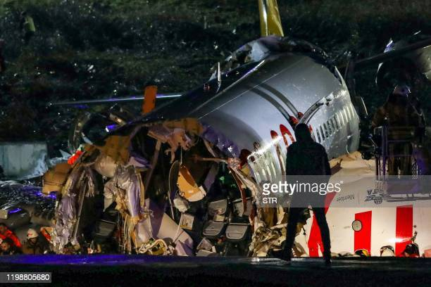 TOPSHOT A picture shows the crash site of a Pegasus Airlines Boeing 737 airplane after it skidded off the runway upon landing at Sabiha Gokcen...