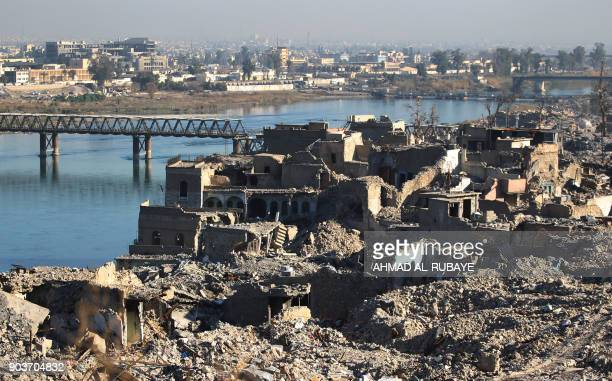 A picture shows the destruction of the old city of Mosul with the city's old bridge over the Tigris river in the background on January 9 2018 Along...