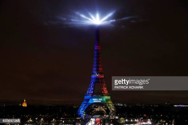 TOPSHOT A picture shows the Eiffel Tower lit in the colours of the Olympic flag during the launch of the international campaign for Paris' bid to...