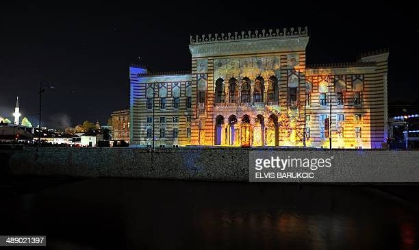 A picture shows the facade of Sarajevo City Hall and National Library building lit with 3D mapping animations figuring flames during a grand...