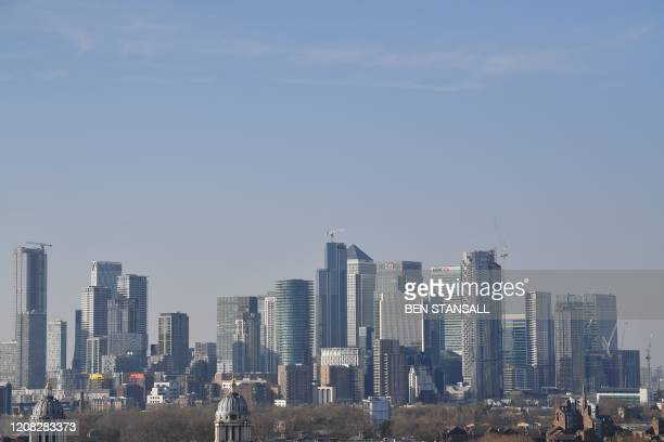 Picture shows the financial towers and bank offices of Canary Wharf from Greenwich Park in London on March 26, 2020 after the government ordered a...