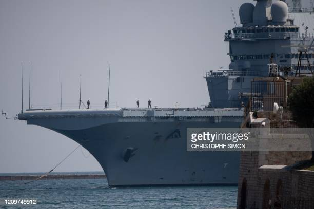 A picture shows the French aircraft carrier Charles de Gaulle on April 12 as it arrives in the southern French port of Toulon with sailors onboard...