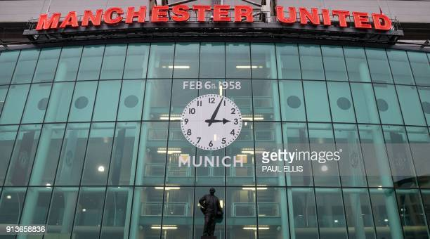 A picture shows the front of Old Trafford stadium with a clock and banners commemorating the 1958 Munich Air Disaster ahead of the English Premier...