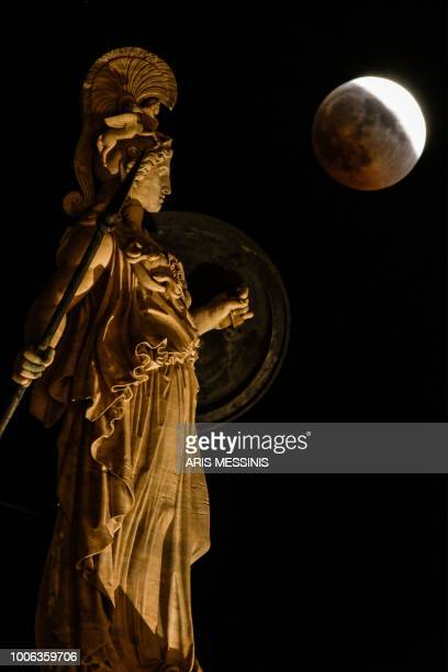 A picture shows the full moon during a blood moon eclipse beside a statue of ancient Greek goddess Athena in central Athens on July 27 2018 The...