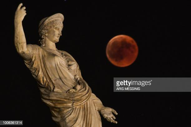 A picture shows the full moon during a blood moon eclipse beside a statue of ancient Greek goddess Hera in central Athens on July 27 2018 The longest...