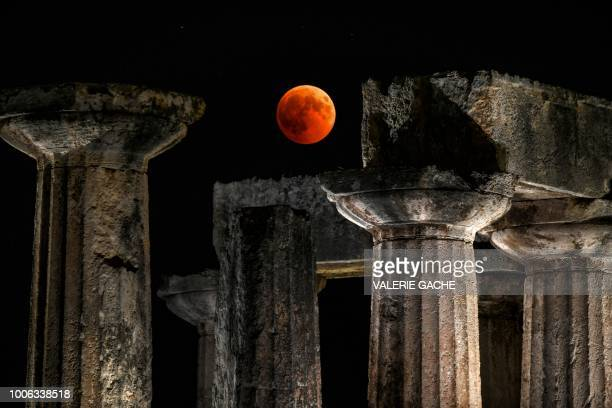 TOPSHOT A picture shows the full moon during a 'blood moon' eclipse over the temple of Apollo in Corinth on July 27 2018 The longest 'blood moon'...
