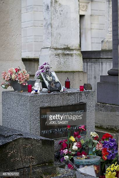 A picture shows the grave of US singer Jim Morrison at the PereLachaise cemetery in Paris on October 16 2014 in Paris From flowers and portraits of...