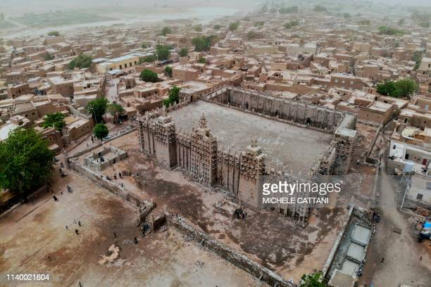 TOPSHOT A picture shows the Great Mosque of Djenne in central Mali during its annual rendering ceremony on April 28 2019 Several thousand residents...