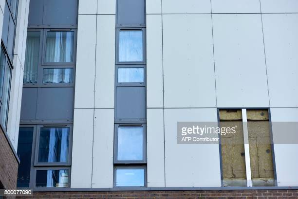 A picture shows the hole where a panel of external cladding was removed from the facade of the Bray residential tower block on the Chalcots Estate in...
