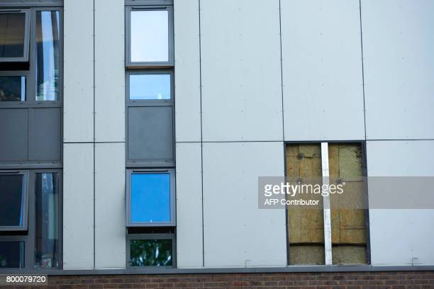 A picture shows the hole where a panel of external cladding was removed from the facade of the Burnham residential tower block on the Chalcots Estate...