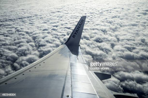A picture shows the logo of Irish lowcost carrier Ryanair on the wing of a plane flying over the Italian Alps on July 1 2015 AFP PHOTO / OLIVIER...