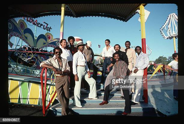 Picture shows the members of the band, Kool & the Gang, posing outside together at an amusement park.