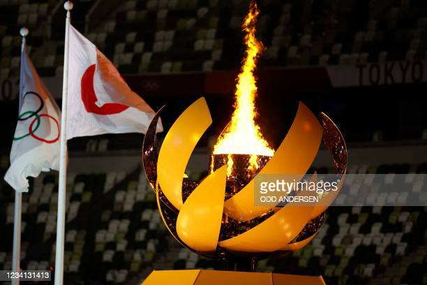 Picture shows the Olympic Flame and Cauldron next to the Japanese and Olympic flags during the opening ceremony of the Tokyo 2020 Olympic Games, at...