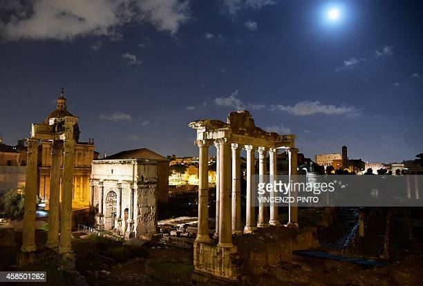 A picture shows the Roman Forum at night with the moon rising in the sky of Rome on November 4 2014 AFP PHOTO / VINCENZO PINTO