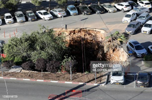 Picture shows the scene after a section of a parking lot collapsed into a sinkhole at Shaare Zedek Hospital in Jerusalem on June 7, 2021.