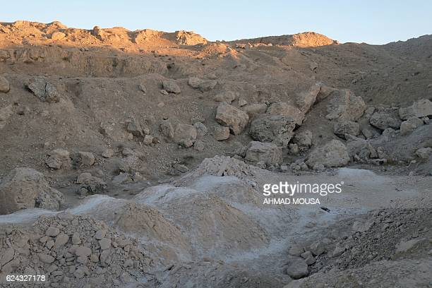 A picture shows the site of a suspected mass grave containing the remains of victims of the Islamic State group on November 18 outside the village of...