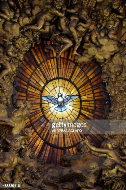 A picture shows the stained glass representing a dove symbol of the Holy Spirit in the apse of St Peter's basilica during a Chrism mass for Holy...