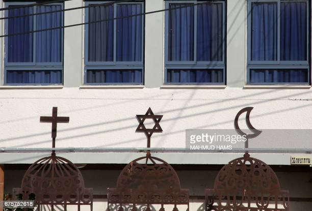 A picture shows the symbols of the three major monotheistic religions the cross for Christianity the Star of David for Judaism and the crescent moon...