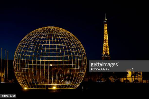 A picture shows the The Symbolic Globe sculpture created in 1995 by Danish engineer Erik Reitzel as the Eiffel Tower is seen in the backround at the...