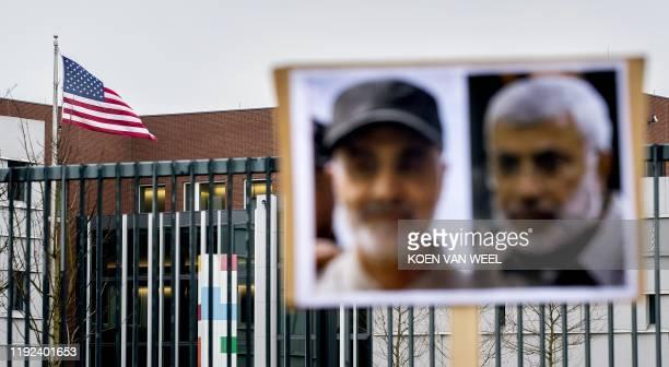 Picture shows the US flag and portraits of Iranian commander Qasem Soleimani and Iraq's Hashed al-Shaabi military network deputy chief Abu Mahdi...