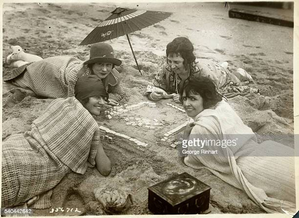 Picture shows women playing Mah Jongg on the beach