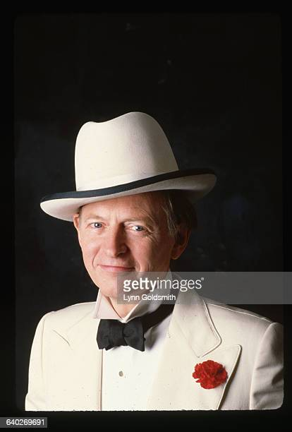 1988 Picture shows writer Tom Wolfe posing in a tuxedo with a white dinner jacket and fedora He is standing in front of a black background and smiling