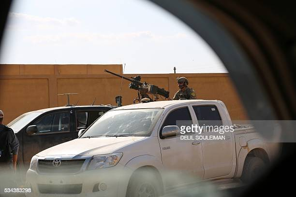 Picture take from inside a car shows an armed man in uniform identified by Syrian Democratic forces as a member of US special operations forces...