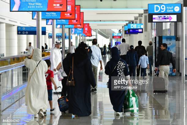 A picture take on September 14 2017 shows people walking at Dubai's International Airport / AFP PHOTO / GIUSEPPE CACACE