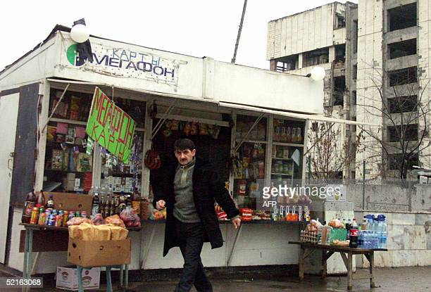 A picture taken 02 February 2005 shows a Chechen man passing by a booth selling telephone cards of Russian mobile phone operator Megafon in central...