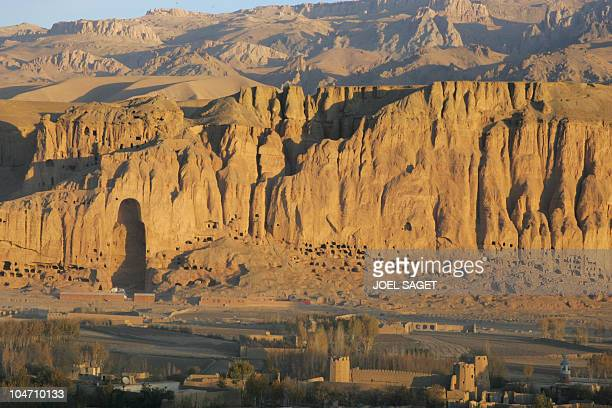 Picture taken 06 November 2005 of the mountains that sheltered the Bamiyan giant Buddhas destroyed by the talibans in 2001 and the village at bottom...