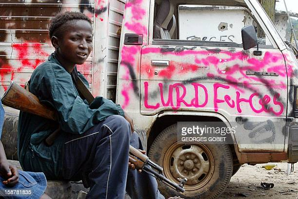WITH 'LIBERIACHILDCOMBATANT' A picture taken 08 August 2003 shows fourteenyearold Chenon Keita resting in the Viatown street of Monrovia a district...