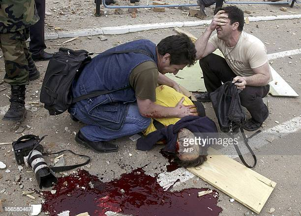 CONTENT ** Picture taken 09 May 2004 shows AP photographer Musa Sadulayev tries to help Reuters news agency journalist Adlan Khasanov who was fatally...