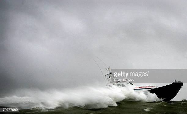 Picture taken 11 January 2007 shows a boat battling with the waves on its way to the harbour A storm front moving over the Netherlands and packing...