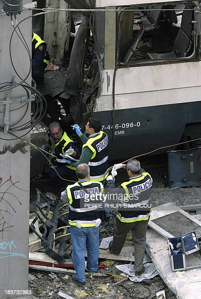 picture taken 11 March 2004 shows Forensic experts seeking for clues around a blast train near Atocha train station after attacks killed 201 people...