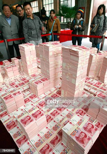 Picture taken 13 October 2007, shows people looking at a model of Beijing's Central Business District made from Chinese yuan notes. China and the...