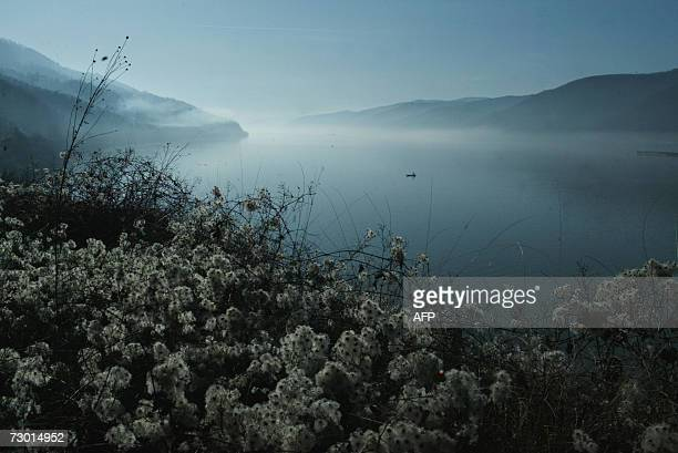 Picture taken 16 January 2007 shows a fisherman boat on the Danube river mist a few kilometers from Golubac on the border with Romania AFP PHOTO...