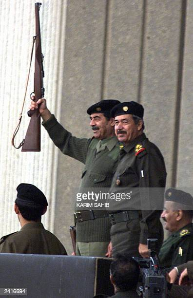 Picture taken 20 November 2000 shows Iraqi President Saddam Hussein holding a gun as he attends with Lieutenant General Ali Hassan alMajid member of...