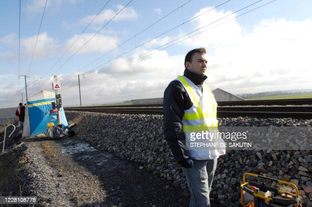 A picture taken 21 November 2007 in Varredes eastern Paris shows a cable worker standing next to damaged cable arteries on East line of highspeed TGV...