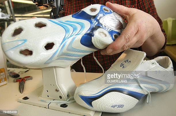 Picture taken 22 March 2006 shows an employee of German sports equipment maker Adidas working on a special edition of the F50 TUNIT football shoe for...