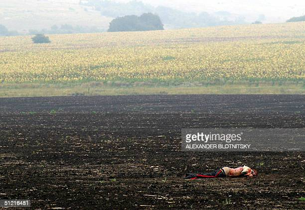 picture taken 25 August 2004 shows a dead body of the Tupolev 154 passenger lying in a field near the place of airplane crash near Gluboky village...