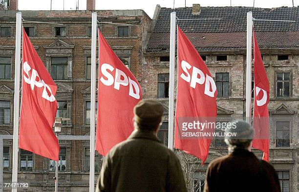 FILES Picture taken 25 January 2002 shows people walking past flags with the logo of the German Social Democrats Party SPD in the western town of...