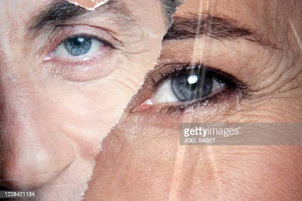 Picture taken 27 April 2007 in Paris, shows partially ripped campaign posters of French right-wing UMP presidential candidate Nicolas Sarkozy and...