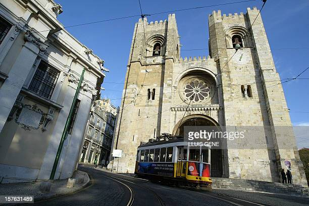 Picture taken 28 November 2003 in Lisbon showing the tramway n° 28 passing in front of the Cathedral Se in the Alfama barrio of the Protuguese...