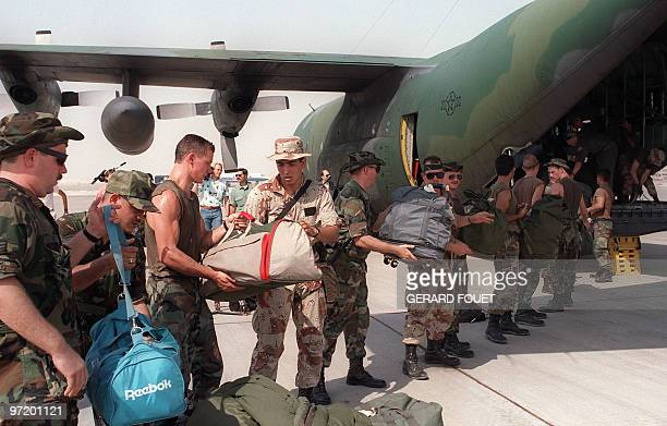 Picture taken 30 August 1990 showing US marines disembark material from a transport plane on a military base a few days after the Iraqi army entered...