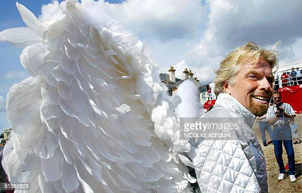 A picture taken 31 August 2003 shows Richard Branson poses with with angel wings prior his flight from Bognor pier in southern British town of Bognor...