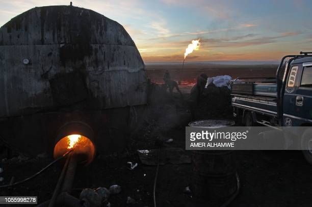 A picture taken at sunset on October 31 2018 shows a primitive oil facility in the town of Zardana in the countryside of the northwestern Syrian...