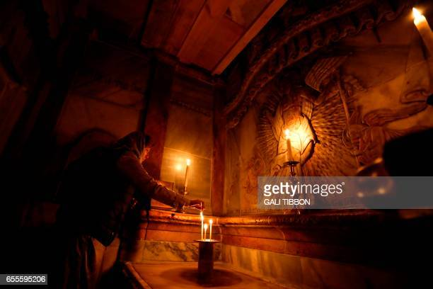 A picture taken at the Church of the Holy Sepulchre in Jerusalems old city on March 20 shows a Christian worshipper praying inside the Edicule...